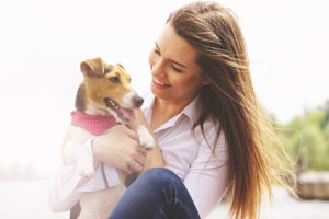 Me and my lovely pet. Portrait of young attractive woman in casual wear looking at dog and smiling while keeping dog on her hands sitting on pier.